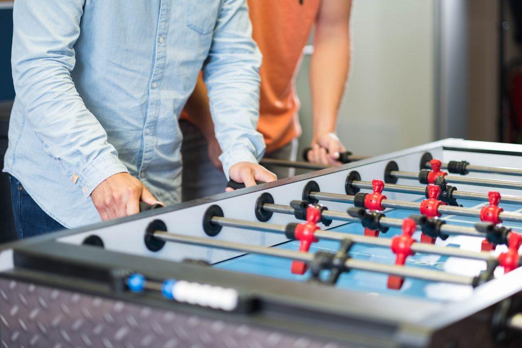 zwei Teammitglieder von NFT spielen eine Partie Tischfußball